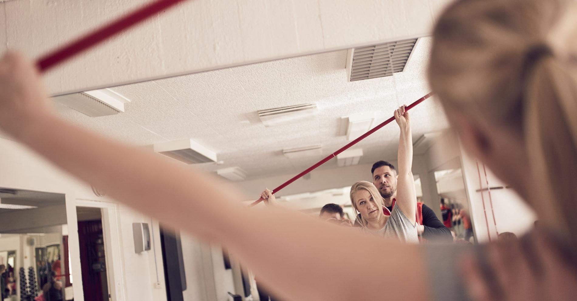 Personal trainer auttaa tekemään lihaskuntolikkeet oikealla tekniikalla.