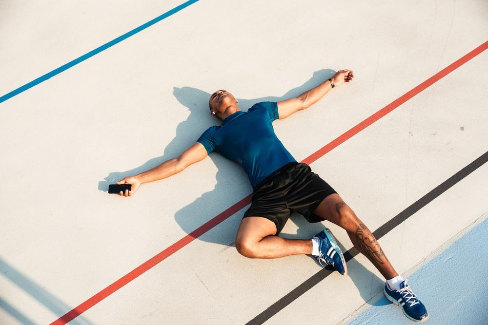 Väsymys treenin jälkeen - mies makaa